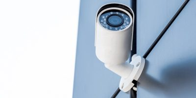 one security camera on blue wall of office building, security system concept